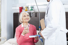 Patient Holding Water Glass And Medicine While Looking At Doctor Stock Photo