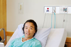 Patient in hospital bed. Looking at tablet Royalty Free Stock Images