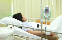 Patient in hospital bed. Woman patient in hospital bed with medical infusion drip tool royalty free stock photo