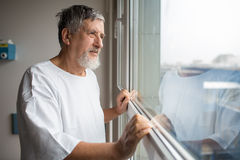 Patient at a hospital, looking from a window in his room Royalty Free Stock Image