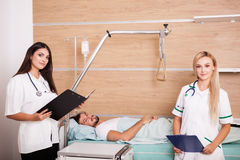 Patient in hospital room next to two nurses Royalty Free Stock Image