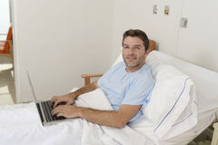 Patient in hospital suffering disease and working at the clinic bed with laptop computer smiling happy Stock Image