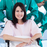 Patient hospitalized in a wheelchair. With doctors on the background Royalty Free Stock Photography