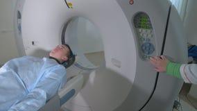 Patient i en nöd- bildläsare för sjukhus MRI Mannen lägger i bildapparaten för magnetisk resonans som gör tomographic scanning arkivfilmer