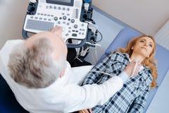 Patient impliqué ayant le contrôle d'ultrason de navires de cou dans la clinique Images libres de droits