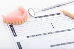 Patient information form and dentures with dental glass with pen Stock Photography
