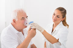 Patient Inhaling Through Oxygen Mask. Female Doctor Looking At Senior Male Patient Inhaling Through Oxygen Mask stock image