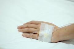 Patient injecté à la main avec l'égouttement IV salin sur le lit d'hôpital photos libres de droits
