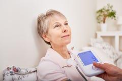 Patient lets nurse measure her blood pressure. For hypertension diagnostics control stock images