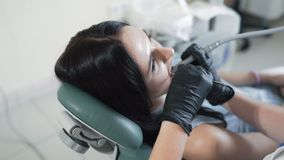 Patient lies in dental chair during dental treatment with modern equipment, slow motion stock footage