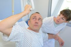 Patient lifting himself out bed with hoist nurse helping Stock Photo