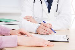 Patient listening intently to a male doctor explaining patient symptoms or asking a question as they discuss paperwork together royalty free stock photography
