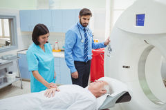 A patient is loaded into an mri machine while doctor and technician watching. At the hospital Royalty Free Stock Image