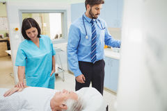 A patient is loaded into an mri machine while doctor and technician watching. At the hospital Stock Image