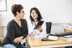 Patient Looking At Doctor Holding Digital Tablet Stock Image