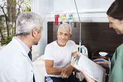 Patient Looking At Doctor While Nurse Holding Reports stock photography