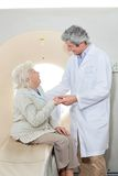 Patient Looking At Doctor. Senior female patient looking at mature male doctor while sitting on CT scan machine Stock Photos