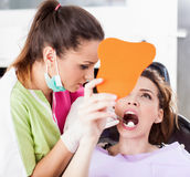 Patient looking in the mirror at her teeth Royalty Free Stock Image