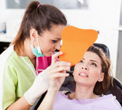 Patient looking in the mirror at her teeth Stock Photo