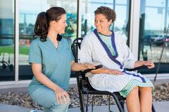 Patient Looking At Nurse While Sitting On Stock Image