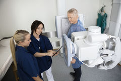 Patient Looking At Radiologists Using Digital Tablet In Hospital Stock Image