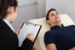 Patient lying on bed while psychologist writing notes Stock Photo