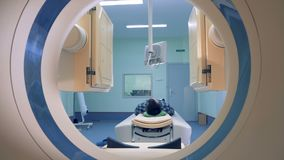 Patient lying on the CT or MRI scanner. Patient`s scanning procedure is starting with CAT-scanner`s elements launching