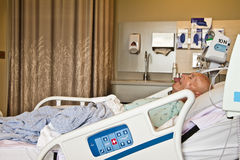 Patient Lying in Hospital Bed. Elderly white male patient sleeping in modern hospital room. Horizontal. Copy space Stock Images
