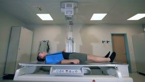 Man lying while tomographic machine scanning him, side view.