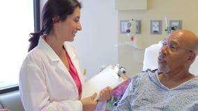 Patient médical de Team Talking To Senior Male dans l'hôpital banque de vidéos