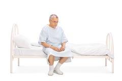 Patient mûr inquiété s'asseyant sur un lit Image stock
