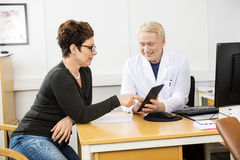 Patient And Male Doctor Communicating Over Digital Tablet. Mature female patient and male doctor communicating over digital tablet in clinic royalty free stock photography