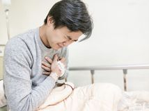 Patient man on hospital bed. Patient man with heart pain on the hospital bed Stock Photography