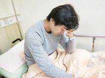 Patient man on hospital bed. Patient man with headache on the hospital bed Stock Photo