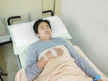 Patient man on hospital bed. Patient man lying on the hospital bed Stock Image