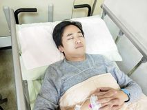 Patient man on hospital bed. Patient man lying on the hospital bed Stock Photography