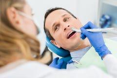 Patient masculin à la procédure dentaire à l'aide de la perceuse dentaire dedans moderne photo libre de droits