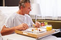 Patient masculin dans le lit d'hôpital mangeant le repas du plateau images libres de droits