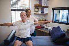 Patient masculin de examen de docteur féminin avec des bras tendus Images libres de droits