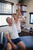 Patient masculin supérieur recherchant tandis qu'épaule de examen de docteur féminin Images stock
