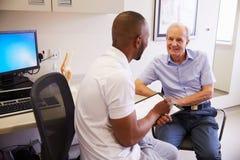 Patient masculin supérieur travaillant avec le physiothérapeute In Hospital Photographie stock libre de droits