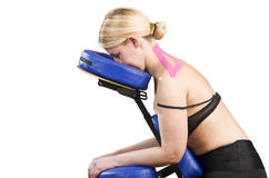Patient in massage chair with pink kinesio tape over white backg Stock Images