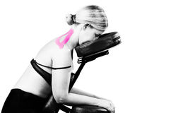 Patient in massage chair with pink kinesio tape  in silhouette s Royalty Free Stock Image