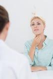 Patient med den öm halsen som besöker doktorn Arkivbilder