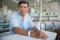 Patient med droppdroppande- och handetiketten Arkivfoton