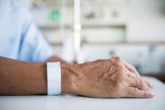 Patient med droppdroppande- och handetiketten Royaltyfri Foto