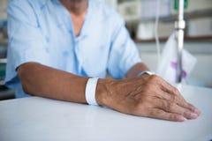 Patient med droppdroppande- och handetiketten Arkivfoto