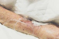 Patient med salthaltigt intravenöst i sjukhuset Royaltyfri Foto