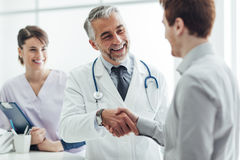 Patient and medical staff. Smiling doctor at the clinic giving an handshake to his patient, healthcare and professionalism concept Stock Photo