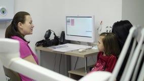 Patient mit dem Kind, das zur zahnmedizinischen Klinik hereinkommt stock video footage